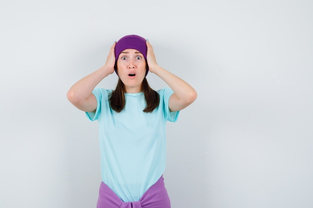 Młoda kobieta w niebieskiej koszulce, fioletowa czapka z rękami na głowie, trzymająca usta otwarte i wyglądająca na zszokowaną, widok z przodu.