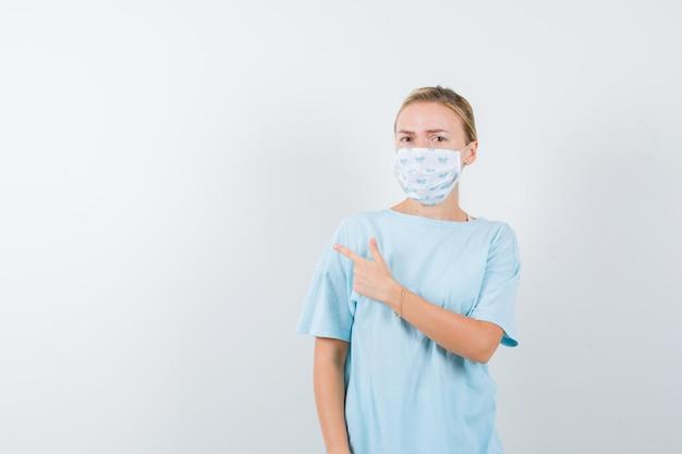 Młoda kobieta w niebieskiej koszulce z maską medyczną