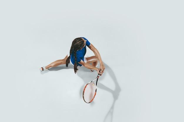 Młoda kobieta w niebieskiej koszuli, grać w tenisa. uderza piłkę rakietą. kryty strzał na białym tle. młodość, elastyczność, moc i energia. negatywna przestrzeń. widok z góry.