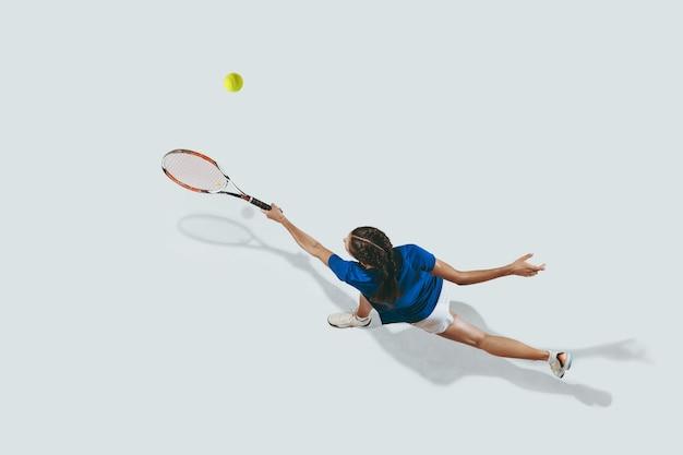 Młoda kobieta w niebieskiej koszuli, grać w tenisa. uderza piłkę rakietą.