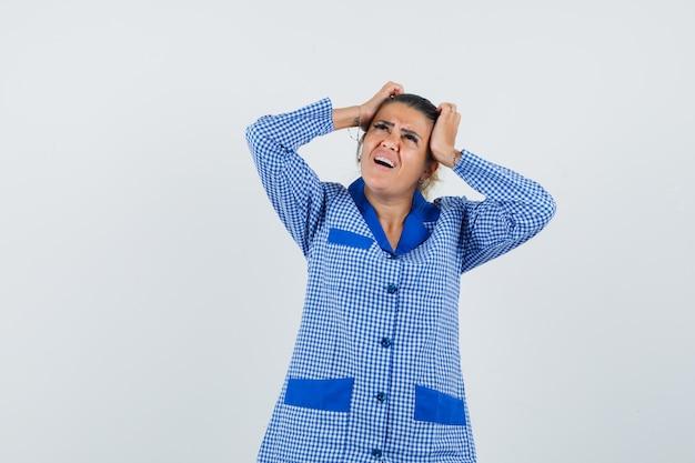 Młoda kobieta w niebieskiej koszuli od piżamy w kratkę kładzie rękę na głowie, ma ból głowy i wygląda na zirytowanego, widok z przodu.