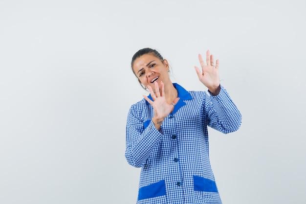 Młoda kobieta w niebieskiej koszuli od piżamy w kratkę pokazuje gest ograniczenia i wygląda ładnie, widok z przodu.