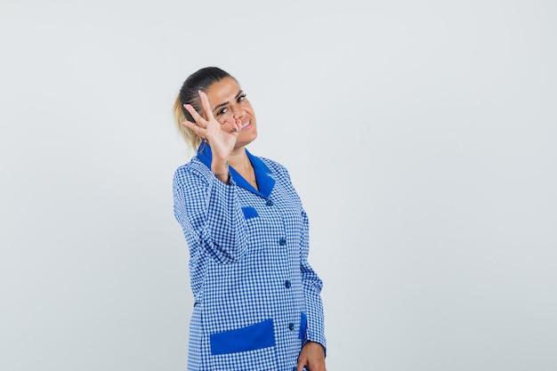Młoda kobieta w niebieskiej koszuli od piżamy w kratkę pokazuje znak ok i wygląda ładnie, widok z przodu.
