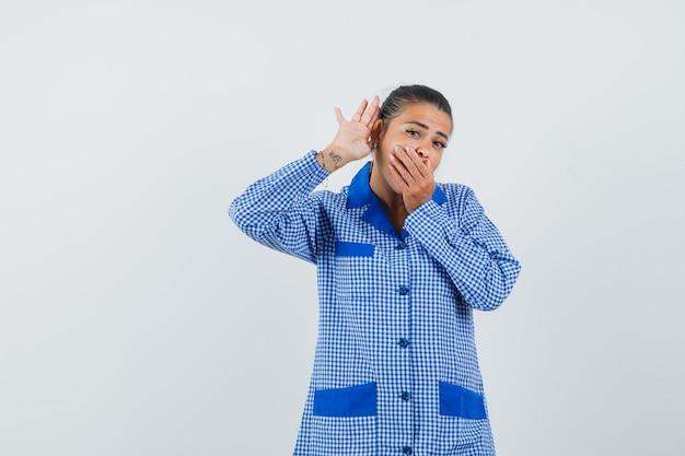 Młoda kobieta w niebieskiej koszuli od piżamy w kratkę trzyma rękę przy uchu, jak słucha kogoś i zakrywa usta ręką i patrzy zdziwiony, widok z przodu.