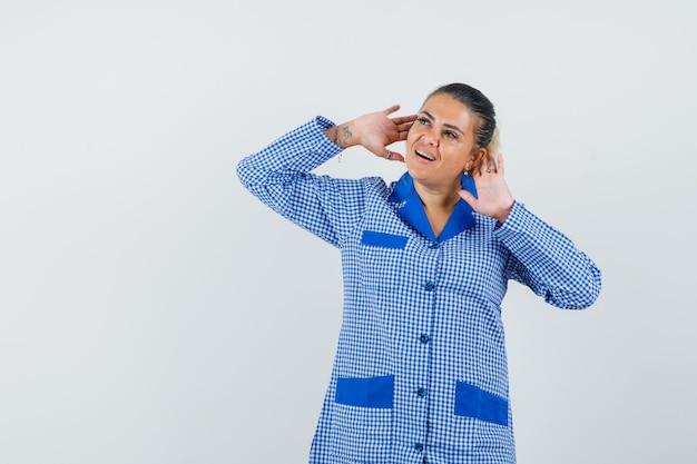 Młoda kobieta w niebieskiej koszuli piżamy bawełniany materiał w kratkę kładąc ręce w pobliżu uszu, jak ktoś słucha i wygląda ładnie, widok z przodu.