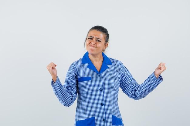 Młoda kobieta w niebieskiej koszuli piżamy bawełniany materiał w kratkę pokazano pozę zwycięzcy i ładny widok z przodu.