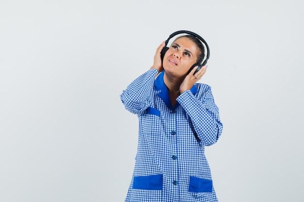 Młoda kobieta w niebieskiej koszuli piżamy bawełniany materiał w kratkę słuchanie muzyki w słuchawkach i patrząc w górę i ładny widok z przodu.