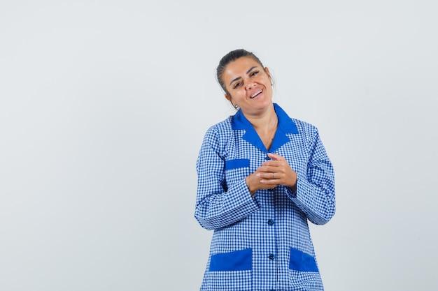 Młoda kobieta w niebieskiej koszuli piżamy bawełniany materiał w kratkę zacierając ręce i patrząc ładnie, przedni widok.