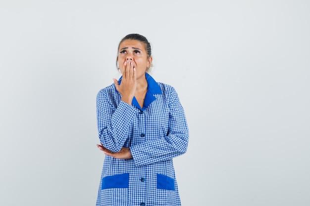 Młoda kobieta w niebieskiej koszuli piżamy w kratkę kładąc rękę na ustach, stojąc w myśleniu gest i patrząc zamyślony, widok z przodu.