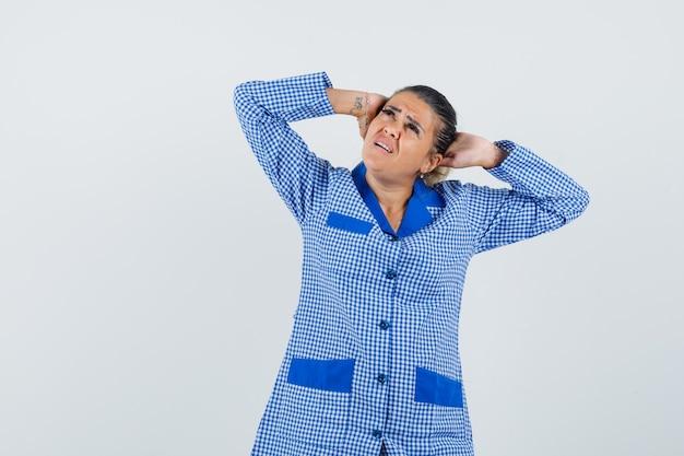 Młoda kobieta w niebieskiej koszuli piżamy w kratkę kładąc rękę za głowę i patrząc zirytowany, widok z przodu.