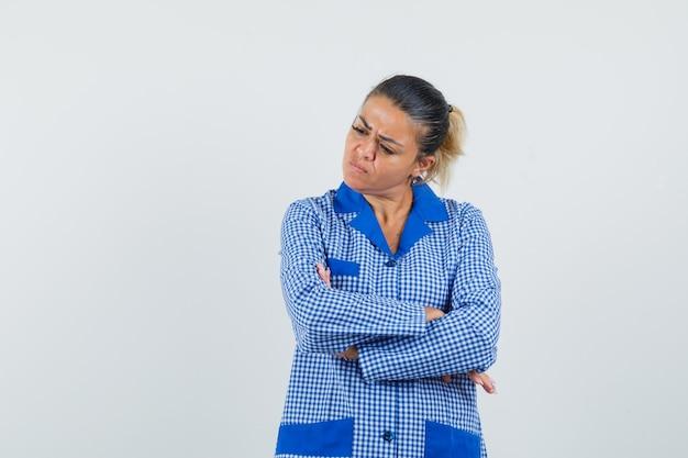 Młoda kobieta w niebieskiej koszuli piżamy w kratkę, stojąc z rękami skrzyżowanymi i patrząc zamyślony, widok z przodu.