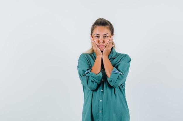 Młoda kobieta w niebieskiej koszuli, podnosząc policzki i wyglądająca na spokojną