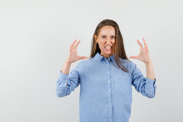 Młoda kobieta w niebieskiej koszuli, podnosząc ręce w agresywny sposób i patrząc wściekle