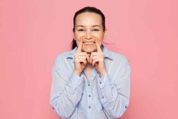 Młoda kobieta w niebieskiej koszuli pozowanie na różowej ścianie