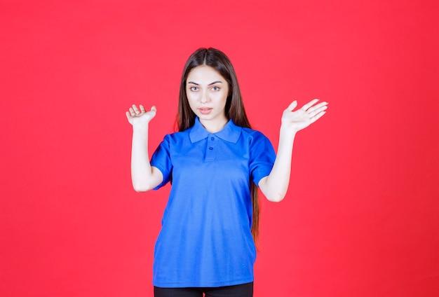 Młoda kobieta w niebieskiej koszuli stojąca na czerwonej ścianie i zatrzymująca coś