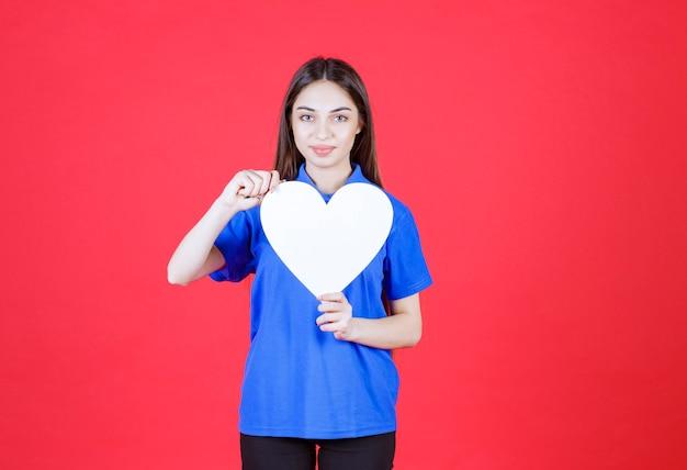 Młoda kobieta w niebieskiej koszuli trzyma białą figurę serca