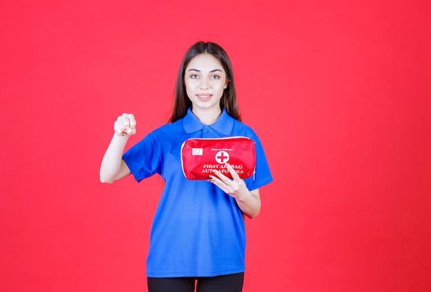Młoda kobieta w niebieskiej koszuli trzyma czerwoną apteczkę i pokazuje pozytywny znak ręki