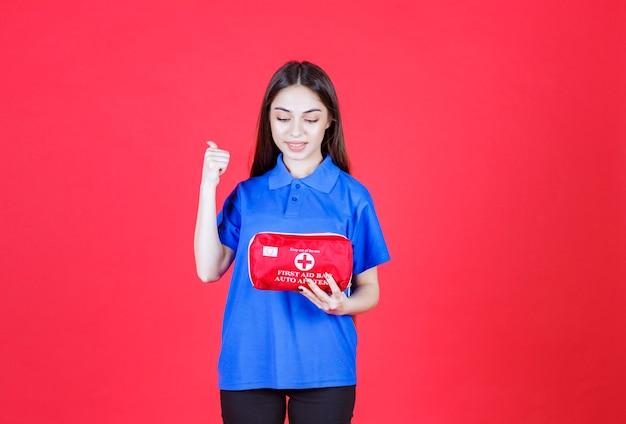 Młoda kobieta w niebieskiej koszuli trzyma czerwoną apteczkę i wskazuje gdzieś