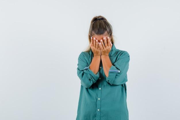 Młoda kobieta w niebieskiej koszuli, trzymając dłoń na jej twarzy i patrząc smutno