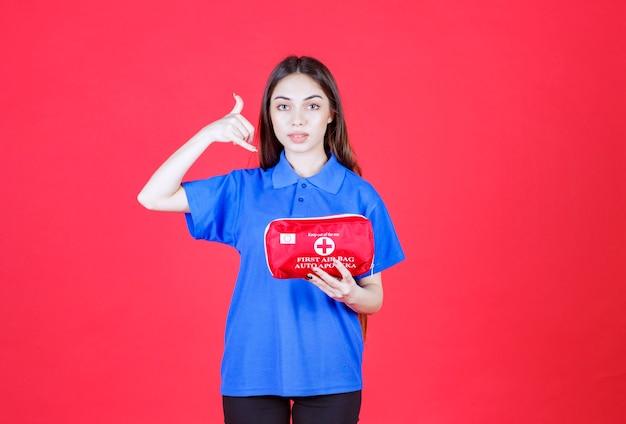 Młoda kobieta w niebieskiej koszuli trzymająca czerwoną apteczkę i prosząca o telefon