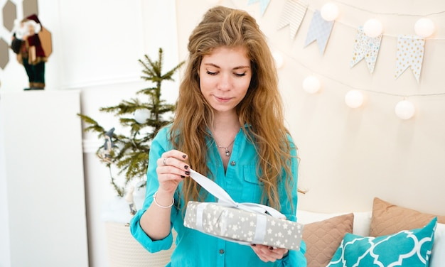 Młoda kobieta w niebieskiej koszuli z prezentem przed świętami bożego narodzenia w domu, przytulne jasne wnętrze