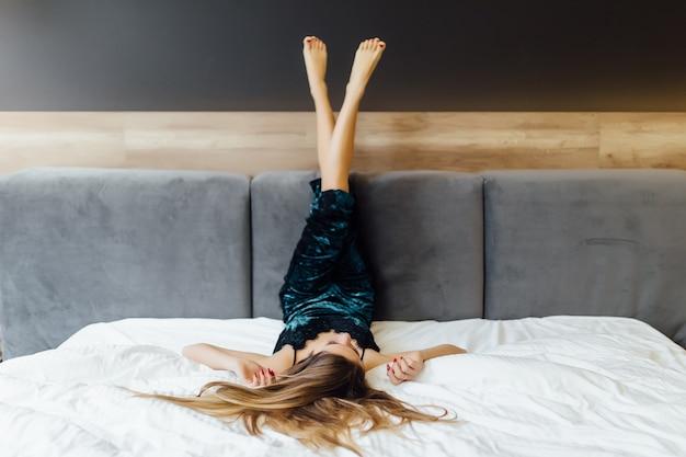 Młoda Kobieta W Niebieskiej Piżamie Pozuje W Sypialni Ze Skrzyżowanymi Nogami Darmowe Zdjęcia