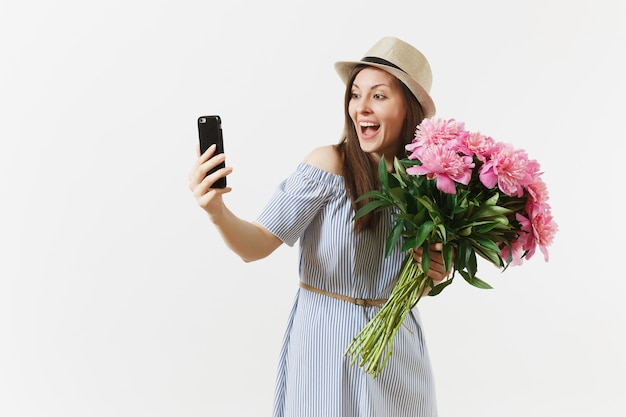 Młoda kobieta w niebieskiej sukience, kapelusz trzymając bukiet kwiatów piękne różowe piwonie, robi selfie na telefon komórkowy na białym tle. walentynki, koncepcja wakacje międzynarodowy dzień kobiet.