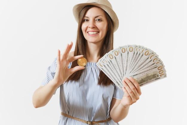 Młoda kobieta w niebieskiej sukience, kapeluszu z długimi włosami, trzymając pakiet dolarów, gotówki, bitcoinów, monety złotego koloru na białym tle. finanse, biznes, koncepcja wirtualnej waluty. skopiuj miejsce