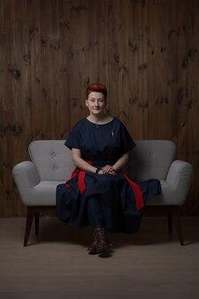 Młoda kobieta w niebieskiej sukience pozuje w studio na szarej kanapie.