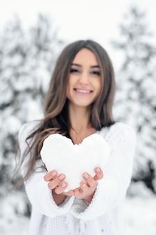 Młoda kobieta w niebieskiej sukience trzyma serce ze śniegu w zimowym lesie.