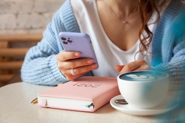 Młoda kobieta w niebieskim ciepłym swetrze czyta wiadomość tekstową z telefonu komórkowego podczas picia kawy. kobieta sprawdza media społecznościowe na swoim smartfonie. styl życia bloggera. planowanie i organizowanie