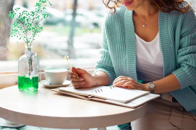 Młoda kobieta w niebieskim ciepłym swetrze siedzi w pobliżu dużego okna kawiarni i pisze notatki