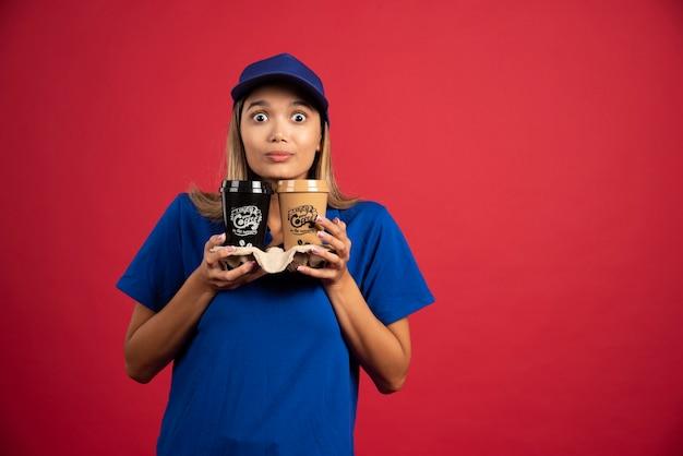 Młoda kobieta w niebieskim mundurze trzyma karton dwóch filiżanek.