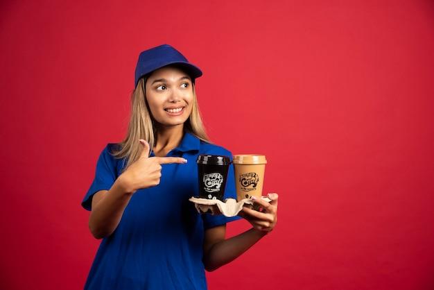 Młoda kobieta w niebieskim mundurze, wskazując na karton dwóch filiżanek.
