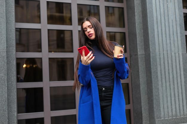 Młoda kobieta w niebieskim płaszczu pije kawę na wynos i rozmawia przez telefon na ulicy. zablokowany średni strzał w czasie rzeczywistym