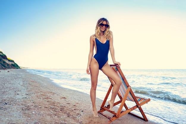 Młoda kobieta w niebieskim stroju kąpielowym relaksuje się na leżaku na plaży