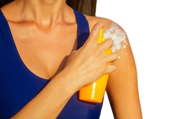 Młoda kobieta w niebieskim stroju kąpielowym trzyma plastikową butelkę z rozpylaczem pomarańczowy pakiet i nakłada krem przeciwsłoneczny na jej ciało. letnia ochrona przed promieniowaniem ultrafioletowym spf na plaży izoluje na białym tle