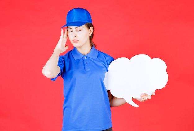 Młoda kobieta w niebieskim stroju pozuje z pustym dymkiem na czerwono.