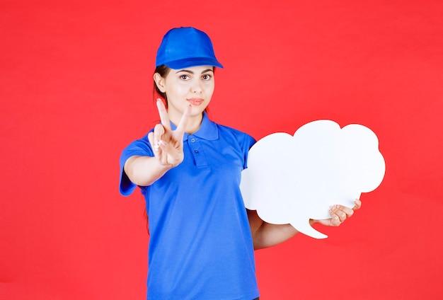 Młoda kobieta w niebieskim stroju z pustym dymku dając znaki na czerwono.