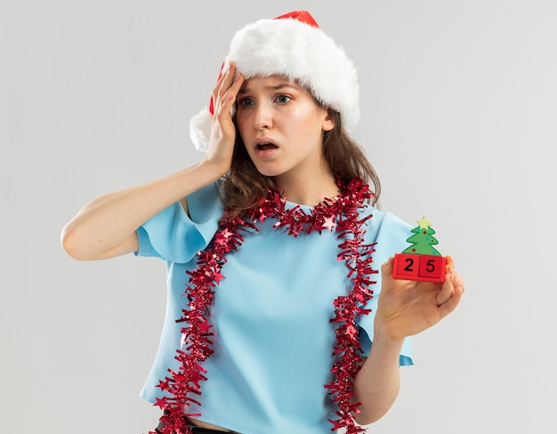 Młoda kobieta w niebieskim topie i czapce mikołaja z blichtrem na szyi trzymająca kostki z zabawkami z datą bożonarodzeniową, patrząc na bok zestresowana i zmartwiona ręką nad głową