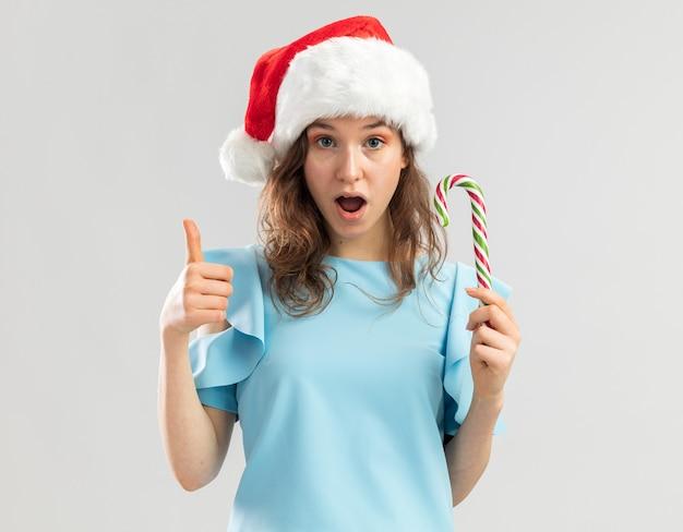 Młoda kobieta w niebieskim topie i santa hat trzyma trzciny cukrowej, wygląda na szczęśliwą i zaskoczoną, pokazując kciuki do góry