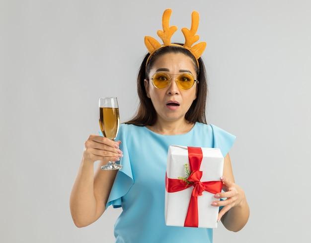 Młoda kobieta w niebieskim topie ubrana w zabawną obręcz z rogami jelenia i żółtymi okularami trzymająca kieliszek szampana i prezent gwiazdkowy wyglądająca na zmartwioną i zdezorientowaną