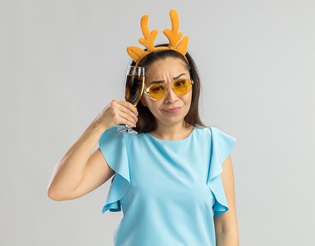 Młoda kobieta w niebieskim topie ubrana w zabawną obręcz z rogami jelenia i żółtymi okularami trzymająca kieliszek szampana, patrząc sceptycznym uśmiechem na twarzy