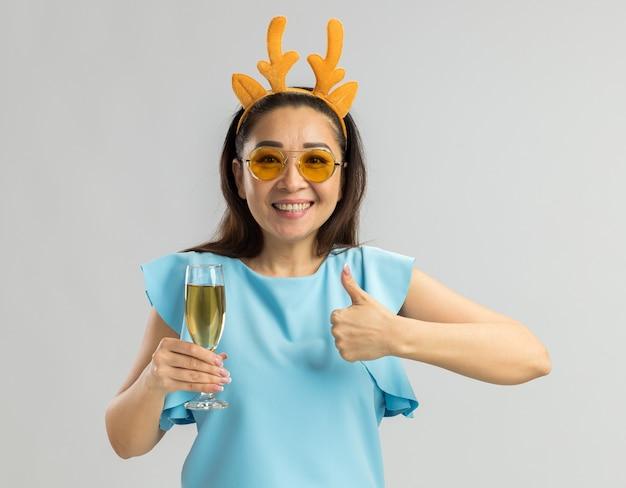 Młoda kobieta w niebieskim topie ubrana w zabawną obręcz z rogami jelenia i żółtymi okularami trzymająca kieliszek szampana wyglądająca na szczęśliwą i wesołą uśmiechniętą, pokazującą kciuki do góry