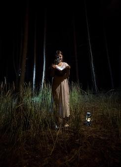 Młoda kobieta w nocnej koszuli czytanie książki w lesie w nocy