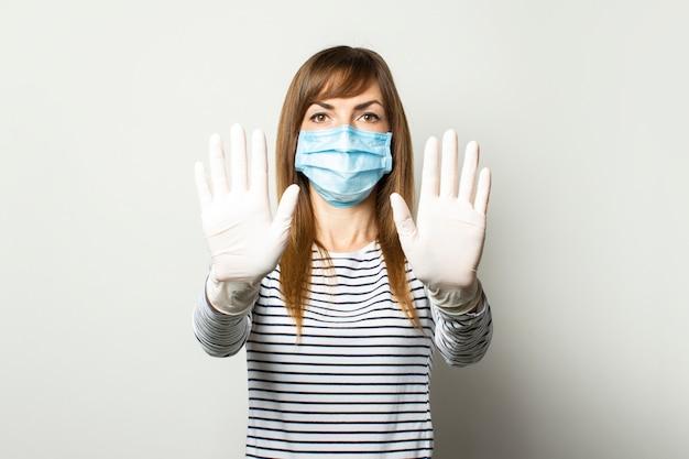 Młoda kobieta w ochronnej masce medycznej i lateksowych rękawiczkach trzyma ręce z przodu i pokazuje widza na lekkiej ścianie na białym tle. koncepcja koronawirusa, pandemii, gest czystych rąk. kopia przestrzeń