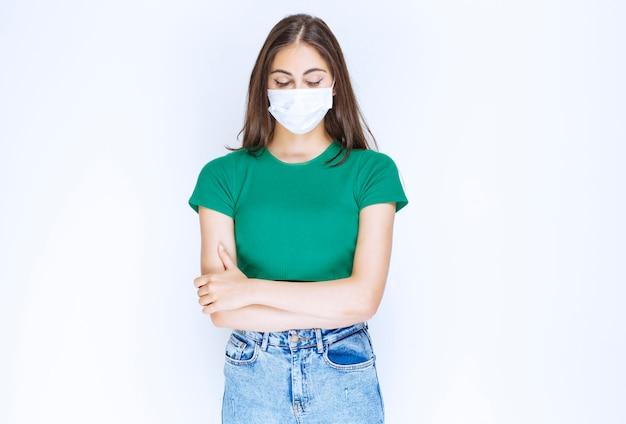Młoda kobieta w ochronnej masce medycznej stoi ze skrzyżowanymi rękami.