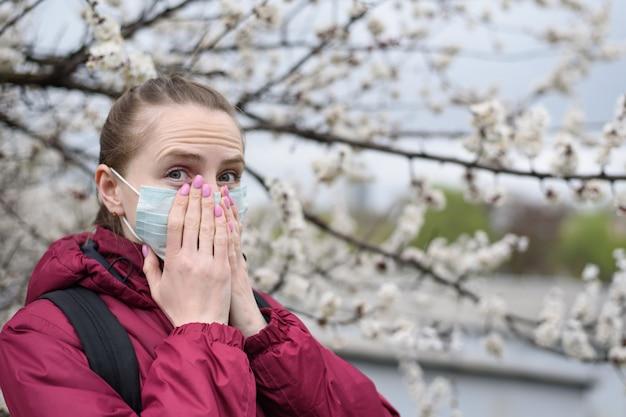 Młoda kobieta w ochronnej medycznej twarzy masce. kwitnące drzewo. alergia wiosenna.