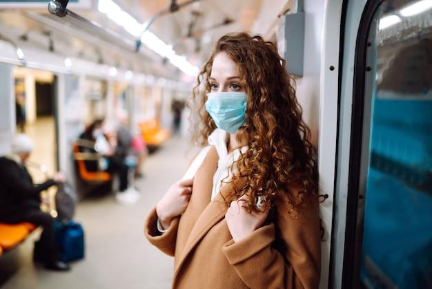 Młoda kobieta w ochronnej sterylnej masce medycznej w samochodzie metra