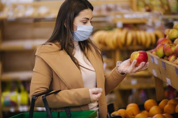 Młoda kobieta w ochronnych rękawiczkach i masce na twarz trzyma w ręku piękne świeże jabłko. piękna, młoda dziewczyna z koszem żywności, wybierając jedzenie przez stoisko z owocami. zakupy podczas kwarantanny. covid-19